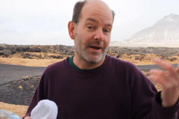 Mark Tretter tries to have a sip of water in Iceland gale during Spring Break.