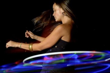 This girl showed off her talents with a hula hoop in her room. After she made it light up, she quickly weaved her body through the hoop without making any mistakes.